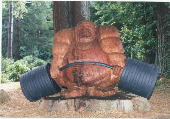 Here is the famous creation of Myers Badura, as sculpted by Eric Wilson. The original powerlifter: Otis Fudpucker. Hewn out of a 150 year old tree stump in California. Myers and Otis hail from Ft. Dick, California where Myers has an absolutely amazing home gym, but where Otis refuses to share his deadlift bar.