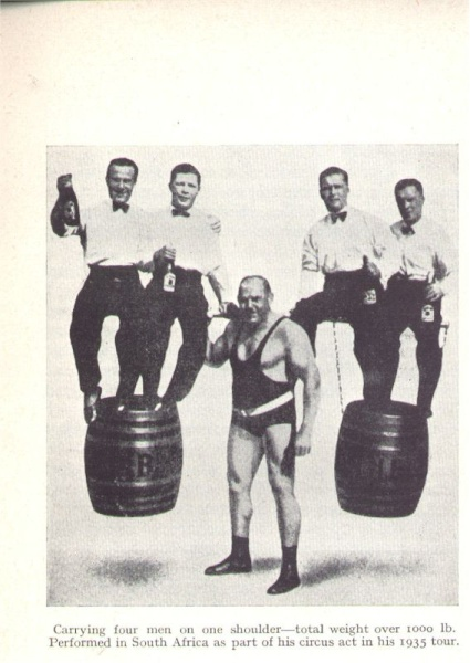 Page 19: Perhaps a staged photo of Hermann Goerner supporting four men and two barrels. Notice the shadow casting pattern on the floor. Notice the very offset placing of the bar on his shoulder. Nothing wrong in those days 