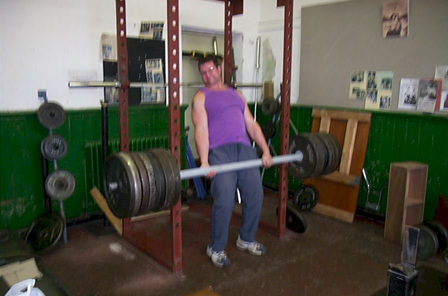 Chris James performing a partial deadlift with 1025lbs on a 2.5-inch thick bar.